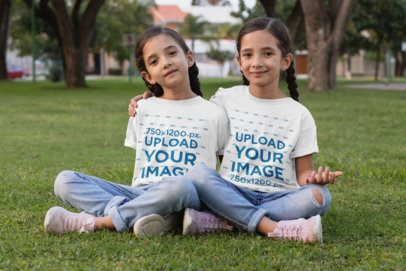 T-Shirt Mockup of Twin Girls Sitting on the Grass 30706