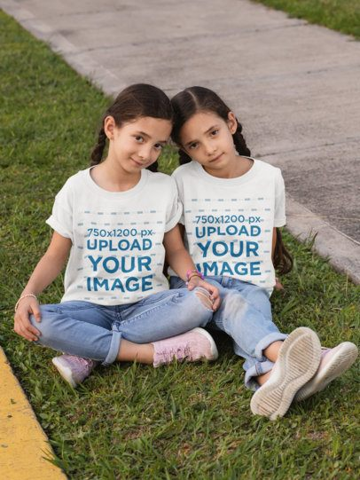 T-Shirt Mockup Featuring Twin Girls Sitting on the Grass 30709