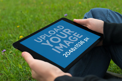Mockup Featuring a Man Holding an iPad Mini While Sitting on the Grass 2053-el