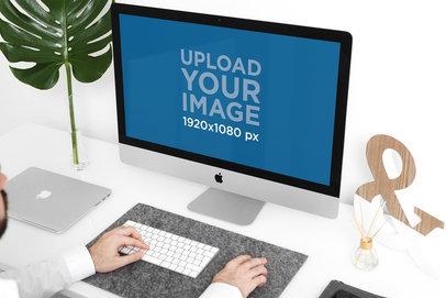 Mockup of a Man Using an iMac in a Minimalist Setting 2139-el