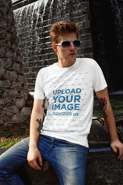 T-Shirt Mockup of a Red-Haired Man Posing Next to a Fountain 2191-el1