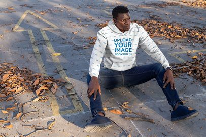 Sublimated Hoodie Mockup of a Man Sitting on the Pavement 31383