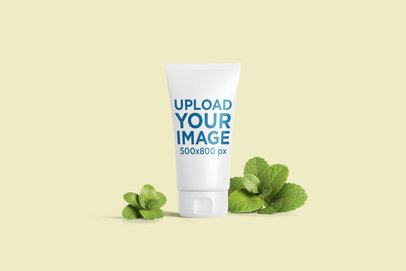 Cosmetic Tube Mockup Featuring Some Mint Leaves and a Plain Background 2400-el1