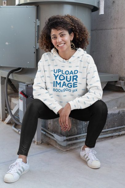 Sublimated Hoodie Mockup of a Happy Woman Sitting by an Industrial Machine 31162