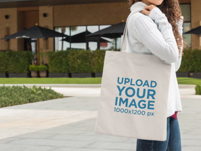 Tote Bag Mockup Carried by a Woman Waiting Outside a11576