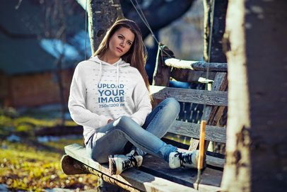 Mockup of a Woman Sitting on a Rustic Bench While Wearing a Hoodie 2782-el1
