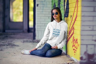 Pullover Hoodie Mockup Featuring a Woman Sitting at an Abandoned Building 2796-el1