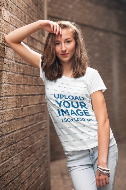 Mockup of a Young Woman Wearing a Customizable T-Shirt and Leaning Against a Brick Wall 2764-el1