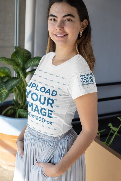 Mockup of a Woman Wearing a T-Shirt with a Customizable Sleeve Next to a Plant 31459