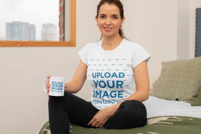 T-Shirt Mockup of a Middle-Aged Woman Holding an 11 oz Mockup and Sitting on Her Bed 31601