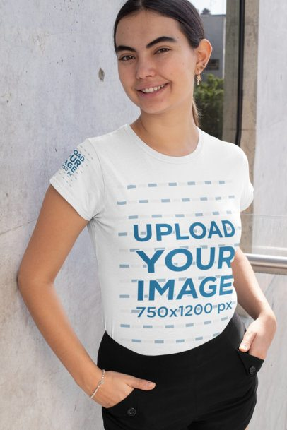 Mockup of a Happy Woman Wearing a T-Shirt with a Customizable Sleeve by a Concrete Wall 31464