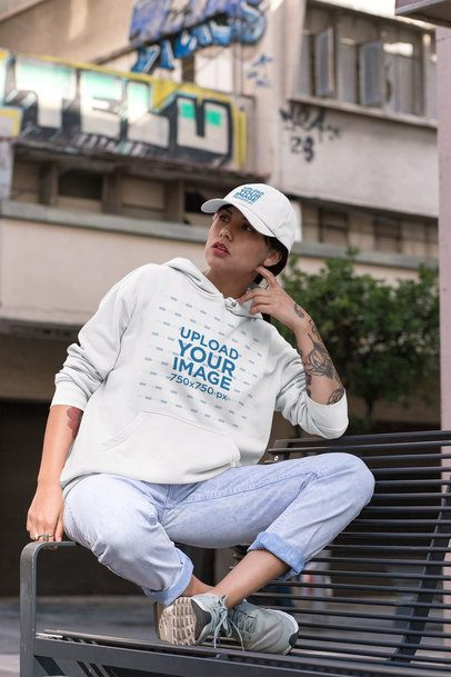Hoodie Mockup of a Woman Wearing a Dad Hat and Sitting on a Bench 31186