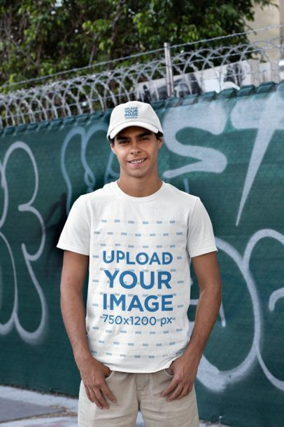 T-Shirt Mockup of a Smiling Man Wearing a Dad Hat Against a Graffiti Fence 31164