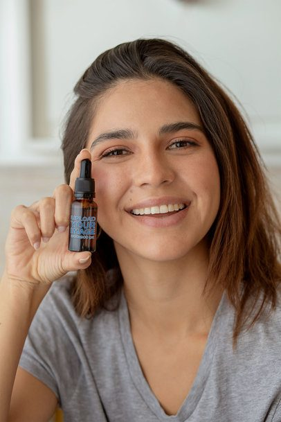 Mockup of a Woman Presenting a CBD Oil Dropper Bottle 32077