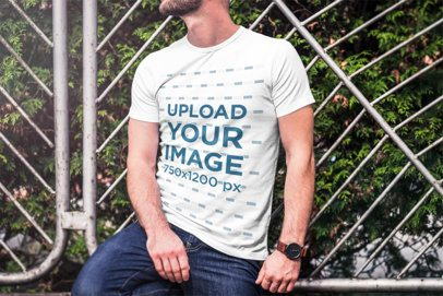 Mockup of a Bearded Man Wearing a T-Shirt and Leaning on a Metal Fence 2969-el1