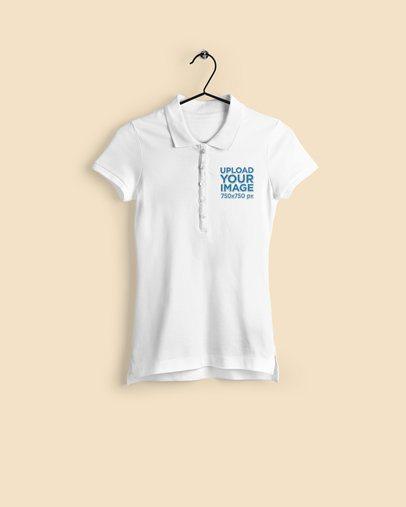 Mockup of a Women's Polo Shirt Hanging Against a Plain Backdrop 3196-el1