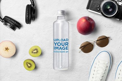 Mockup Featuring a Glass Water Bottle Placed on a Clear Surface and Surrounded by Different Items 3155-el1