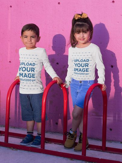 Long Sleeve Tee Mockup Featuring Two Kids Posing Against a Pink Wall 31675