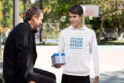 Pullover Hoodie Mockup of a Young Man Giving His Dad a Present by a Basketball Court 33092