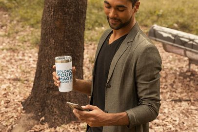Travel Mug Mockup of a Man Looking at His Phone 31837