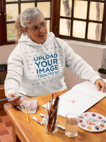 Pullover Hoodie Mockup Featuring a Senior Woman Painting at Home 32207