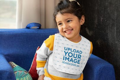 Mockup of a Little Girl Wearing a Baby Bib at Home 32512