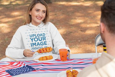 Hoodie Mockup of a Woman Eating a Snack on the 4th of July 33037