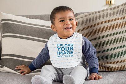 Bib Mockup Featuring a Happy Baby Boy Sitting on a Couch 32522