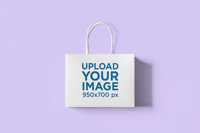 Minimal Mockup Featuring a Gift Bag Lying Over a Plain Color Surface 3479-el1