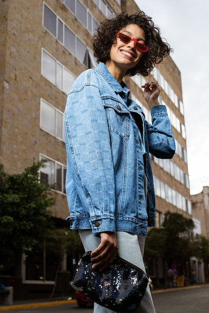 Denim Jacket Mockup Featuring a Woman Posing by a Tall Building 32572