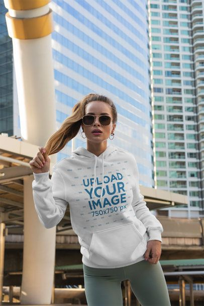 Pullover Hoodie Mockup Featuring a Woman Posing in Front of Some Tall Buildings 3554-el1
