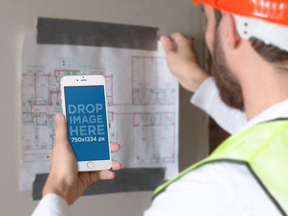 iPhone 6 Mockup of an Architect Reviewing a Blueprint a12425wide