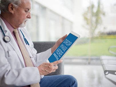 iPad Mockup in Portrait Position of a Senior Doctor Sitting on a Couch 12445b
