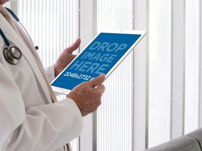 Mockup Featuring a Senior Doctor Holding an iPad in Portrait Position 12441