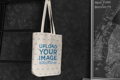 Mockup of a Sublimated Tote Bag Hanging by a Framed Map 3142-el1