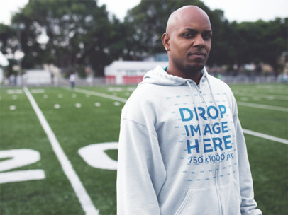 Full Zip Hoodie Mockup of a Young Black Man at a Football Field a12451