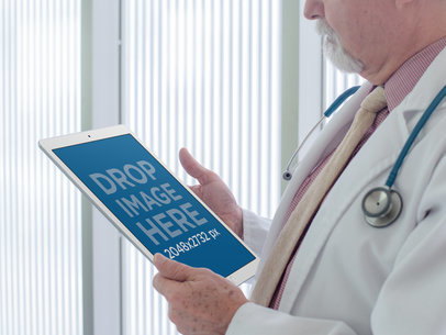 iPad Pro in Portrait Position Mockup Held by a Doctor in a White Hall a12448wide