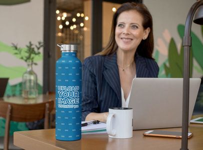 Mockup of a Woman with an Aluminum Bottle on Her Office Desk 33485