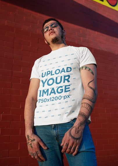 T-Shirt Mockup of a Tough-Looking Man Posing in Front of a Red Brick Wall 32817