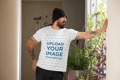 Mockup of a Man Wearing a Customizable T-Shirt and Looking Through a Window 32835