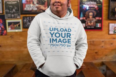 Cropped Face Mockup of a Smiling Man with a Hoodie at a Bar 32860