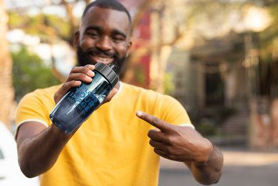 Mockup of a Smiling Man Pointing at a Bike Bottle 33518