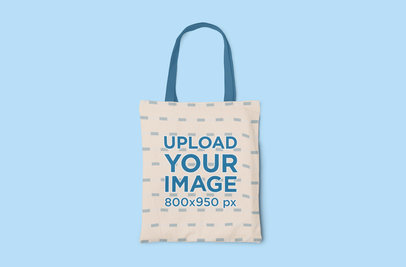 Mockup of a Sublimated Tote Bag with Customizable Strap on a Colored Surface 3122-el1