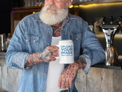 Mockup of a Tattooed Man Holding a 20 oz Beer Stein by a Bar 33449