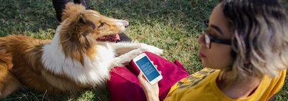 Mockup of an iPhone in Portrait Position Featuring a Woman Sitting in the Garden with Her Dog 12796wide