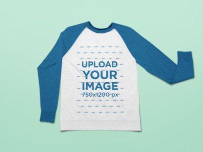 Mockup of a Raglan Sweatshirt Laid on a Customizable Surface 25500