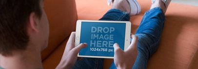 White iPad Mini Mockup Featuring a Young Teen Playing on his Living Room Couch a13058w