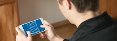 iPhone 7 Plus Mockup of a Teenage Boy Playing Indoors 13055