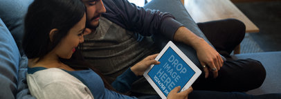 Mockup of a Couple Sitting in the Living Room Staring at an iPad in Landscape Position 13103wide