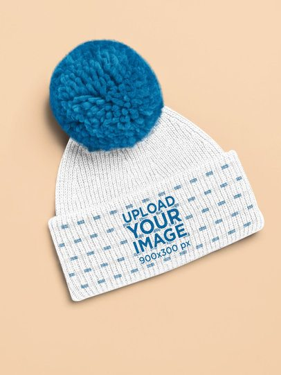 Mockup of a Pom-Pom Beanie Lying on a Colored Surface 25744